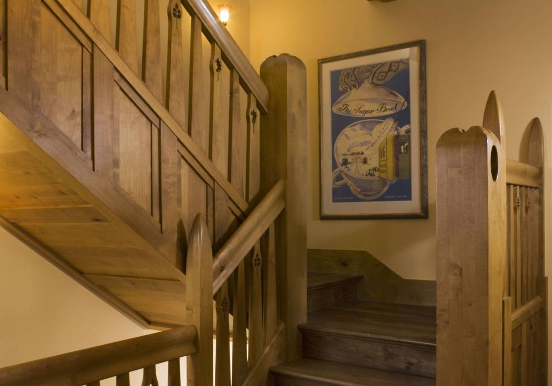 Carved newel posts and water jet cut balusters crafted from stained alder wood form the central skylit stairway of this home.