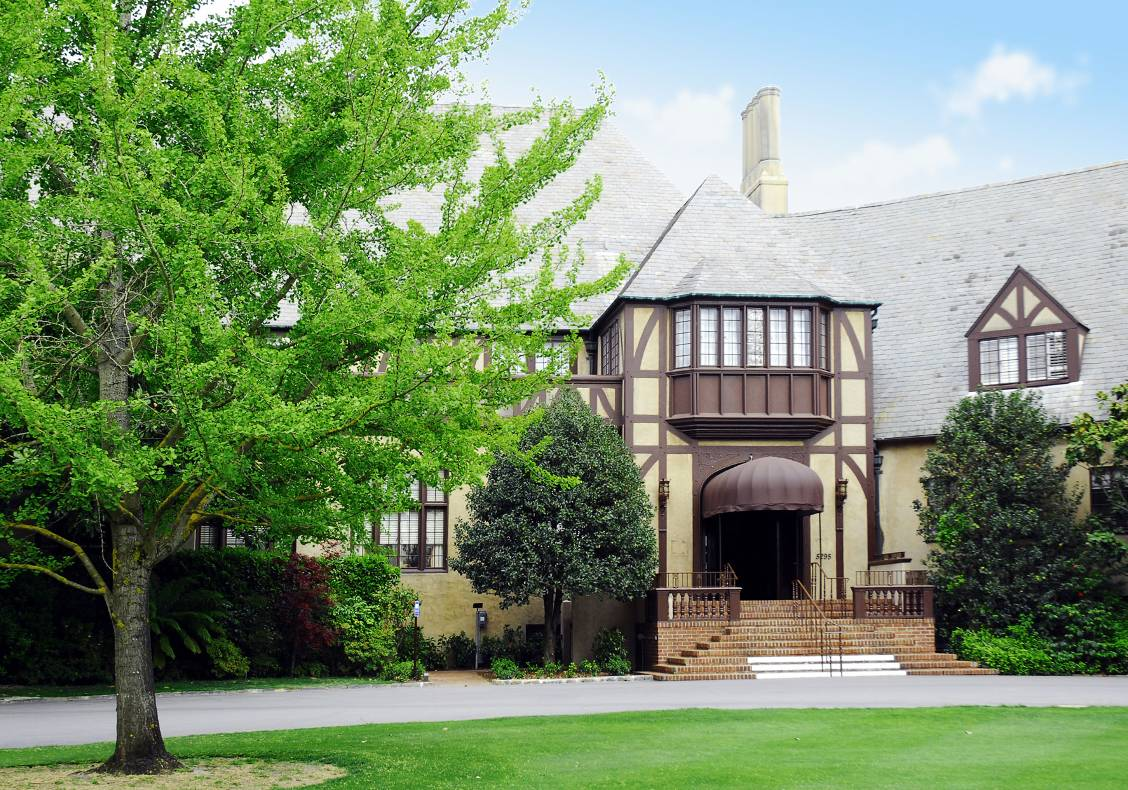 A beautiful, full green tree frames the peaceful main entrance to the country club, which is graced by a wooden balustrade and brick steps that cascade down to the main walkway.