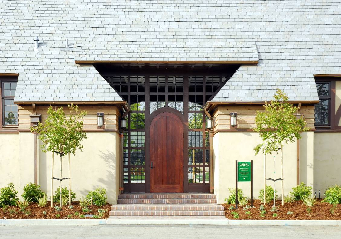 Blending both traditional and modern detailing, this simple wood plank door surrounded by glazing marks one of the entrances to the country club's new Aquatic Center.