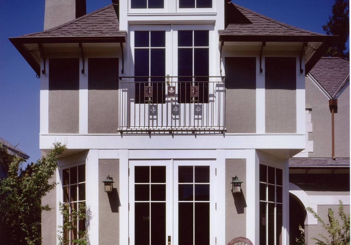 Voysey-inspired details include hammered iron soffit brackets, waterjet cut railing details, rendered walls with white trim, and hip dormers.