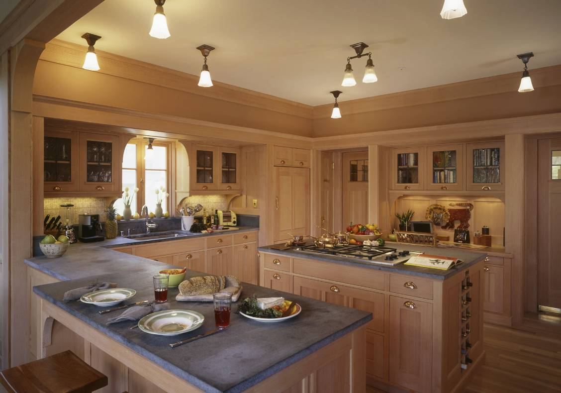 Soapstone counters and ceiling-mounted light fixtures; cabinet doors are fitted with seeded glass set in lead frames.