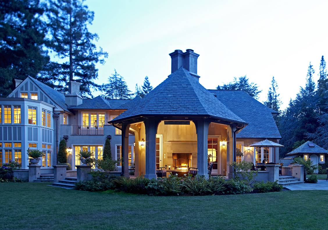 Outdoor room with heavy timber frame, fireplace, slate roof, Lutyens chimney caps, evening view.
