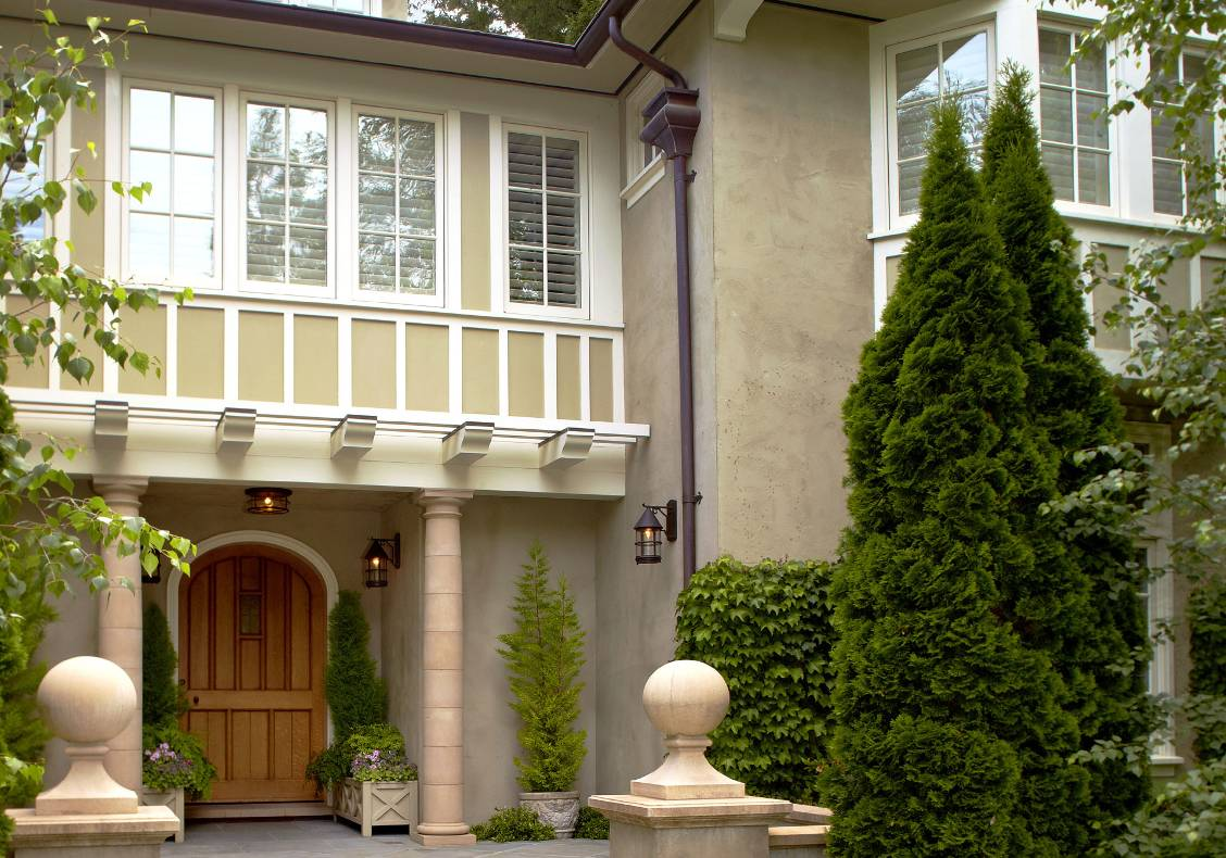 Cast stone bollards, bluestone porch steps, rendered gables, quartersawn oak door.