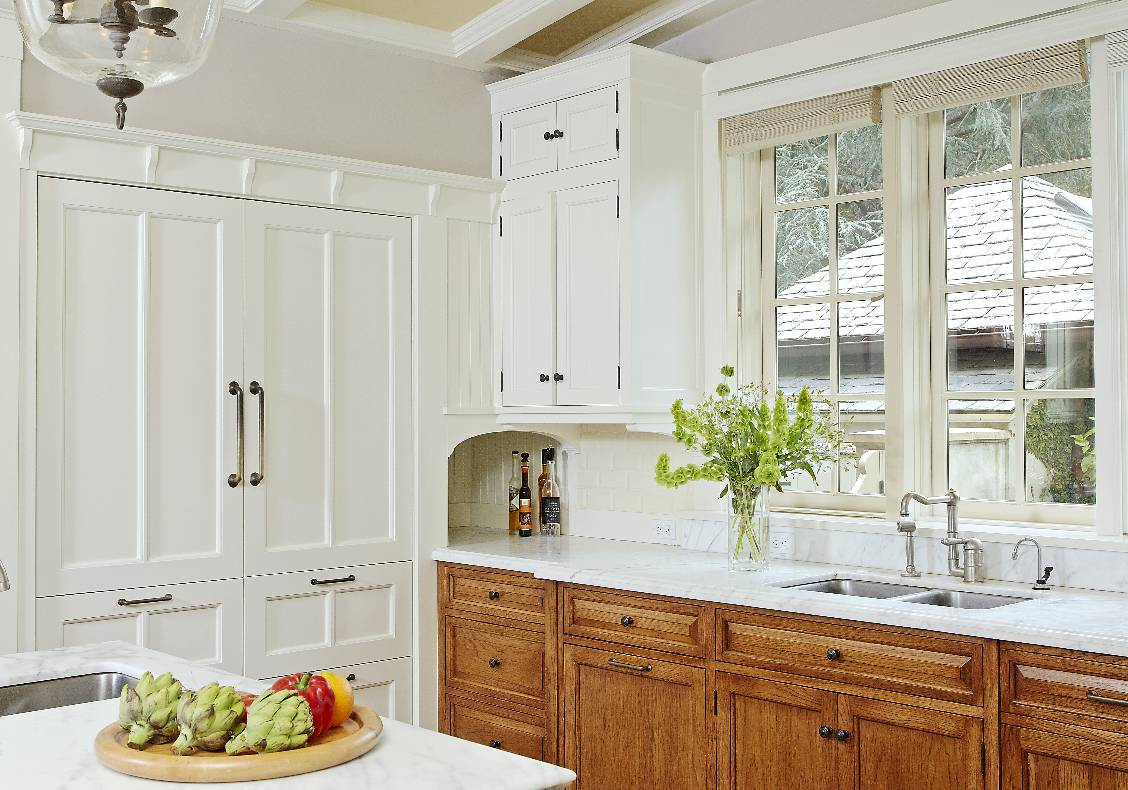 English country kitchen with vaulted ceiling and apothecary lantern, integrated refrigerator, calacata counters, and hickory cabinets.