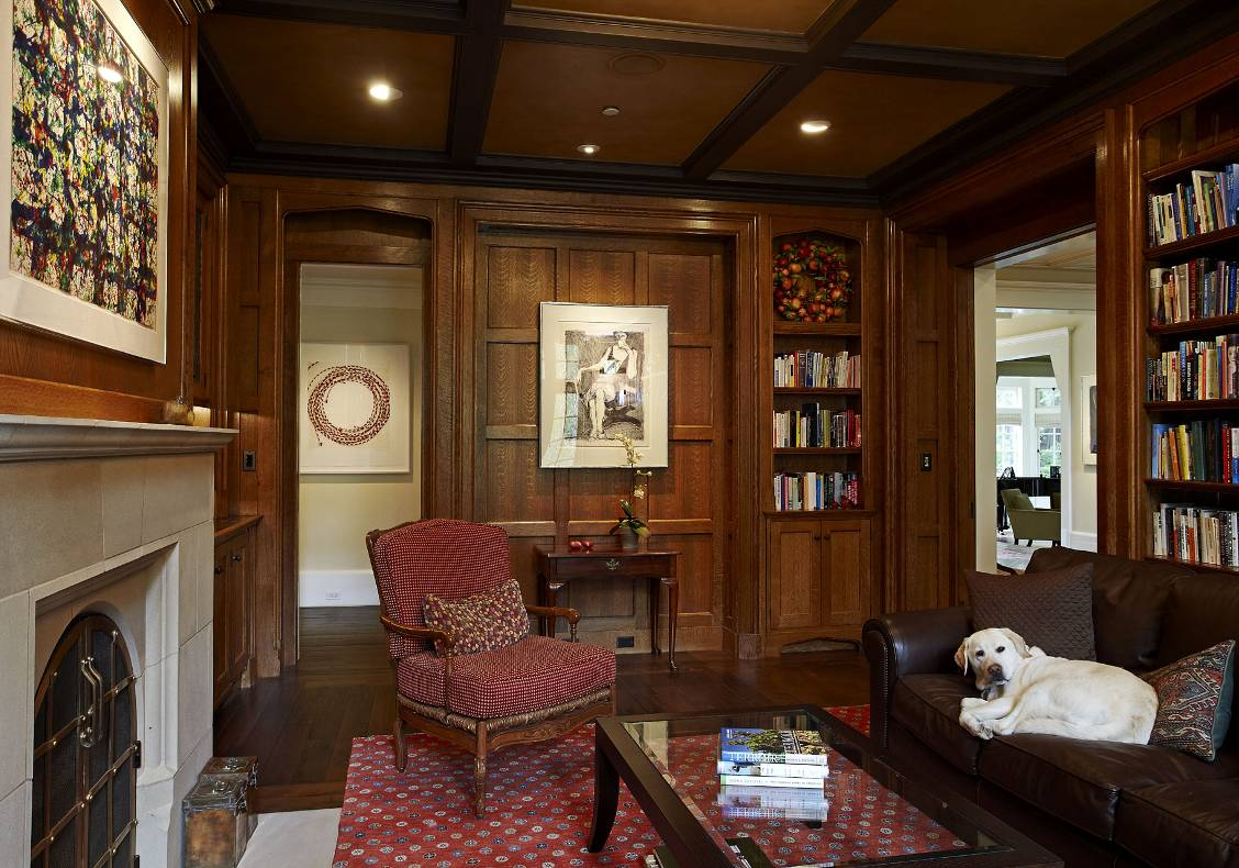English country manor oak library with cast stone Lutyens fireplace surround, bronze fireplace doors, and leather ceiling.