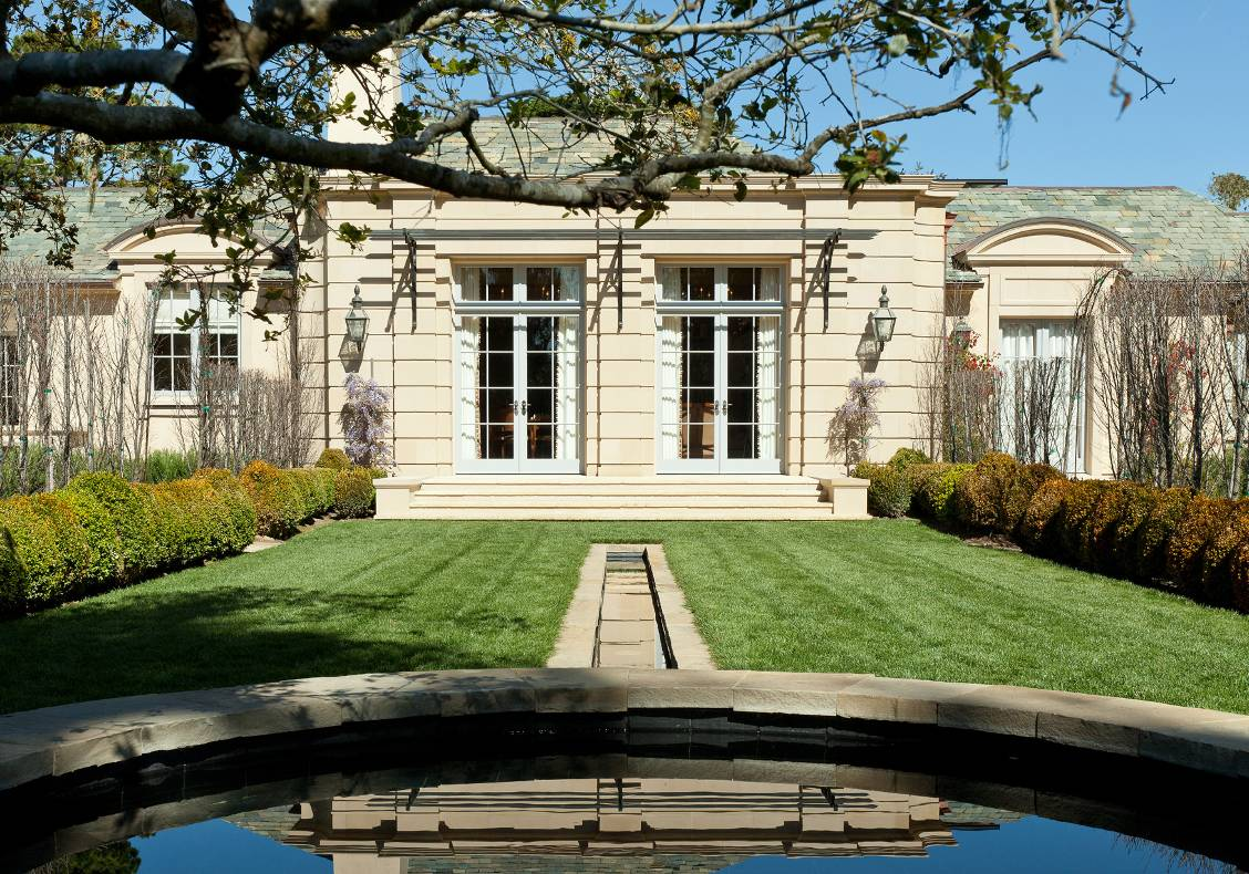 The paired French doors of the library face the lawn and a stone-bordered rill leading to a circular fountain.