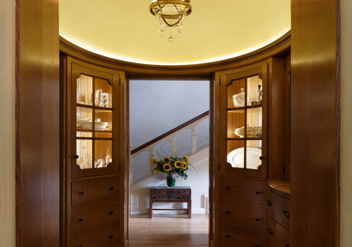 The butler's pantry's floor pattern, domed ceiling and art glass window play off the room's oval geometries.