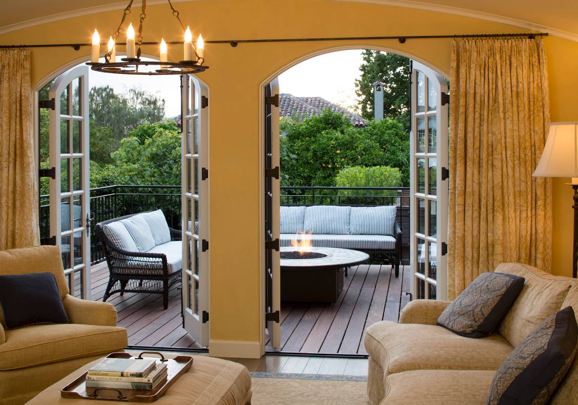 The new deck overlooking the backyard features a central fire table with a mosaic top.
