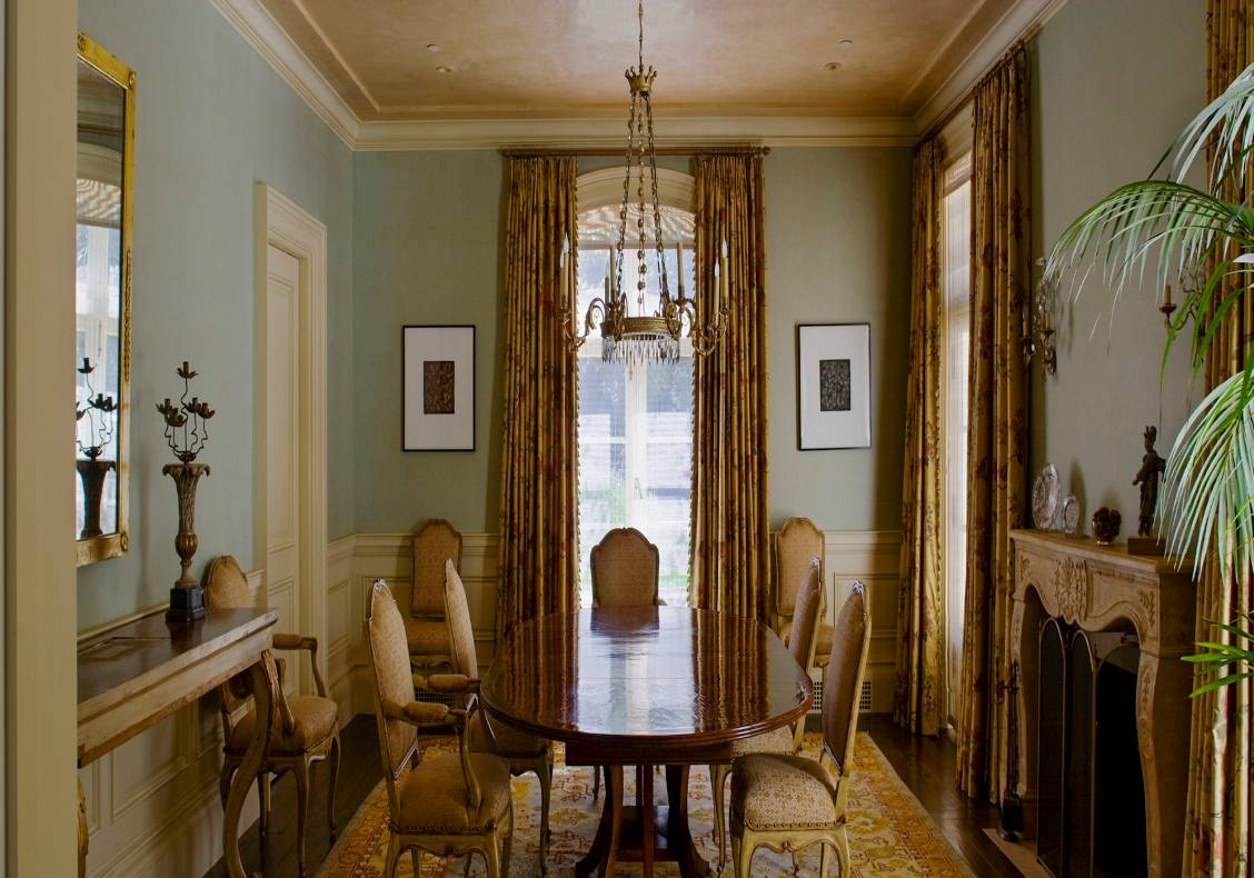 The dining room's pale green walls and creamy white wainscot are a counterpoint to the golden hue of the jacquard curtains and Persian carpet.