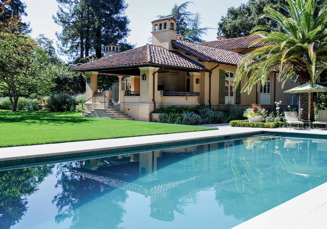 The outdoor loggia surveys the rear lawn and pool.