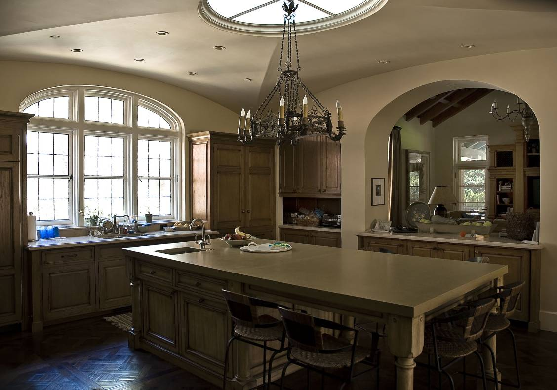 The large kitchen island provides a central gathering point and informal dining space for the family. The ceiling has a large elliptical skylight that fills the room with warm, natural light.