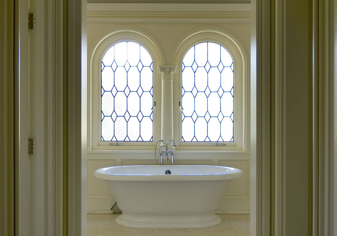 The master bathroom features leaded glass arched windows.