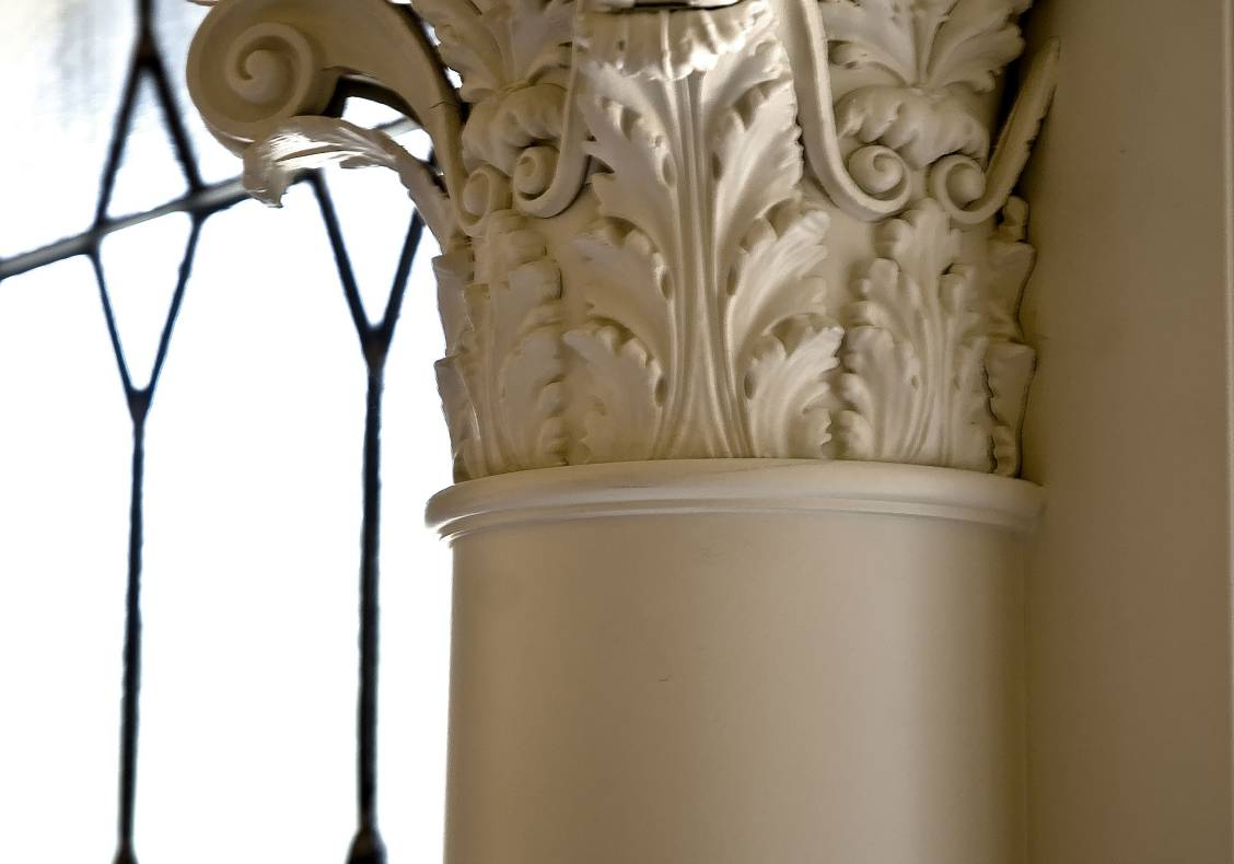 A Corinthian capital graces the wall between the master bathroom's leaded glass windows.