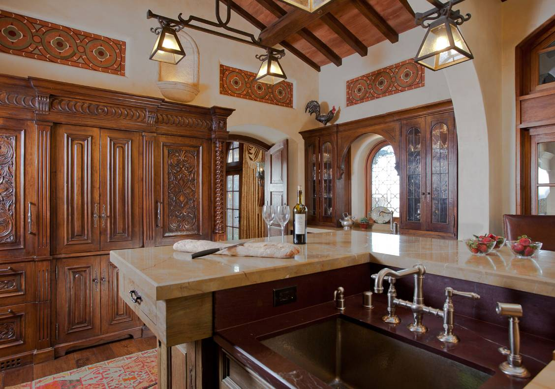 The rusticity of the kitchen island complements the refinement of the surrounding cabinets.