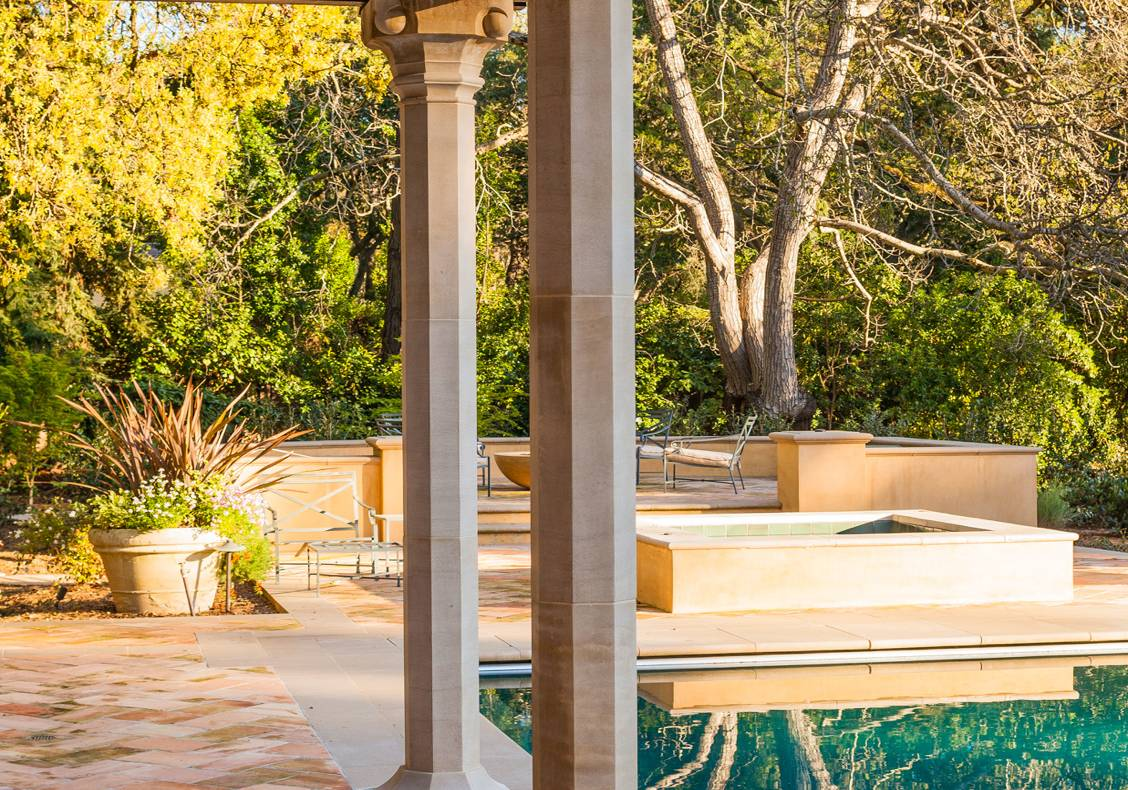 A wooden trellis on stone columns provides shade next to the pool.