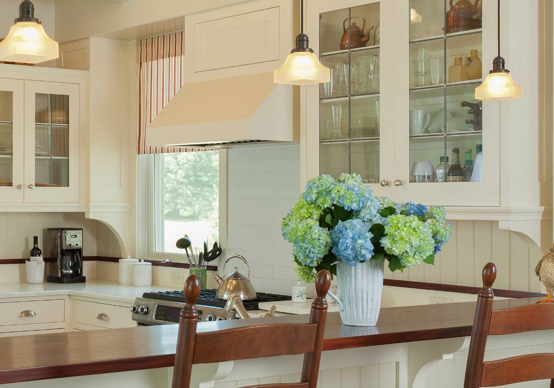 The leaded glass windows of the upper cabinets and the scalloped brackets make this simple kitchen special.