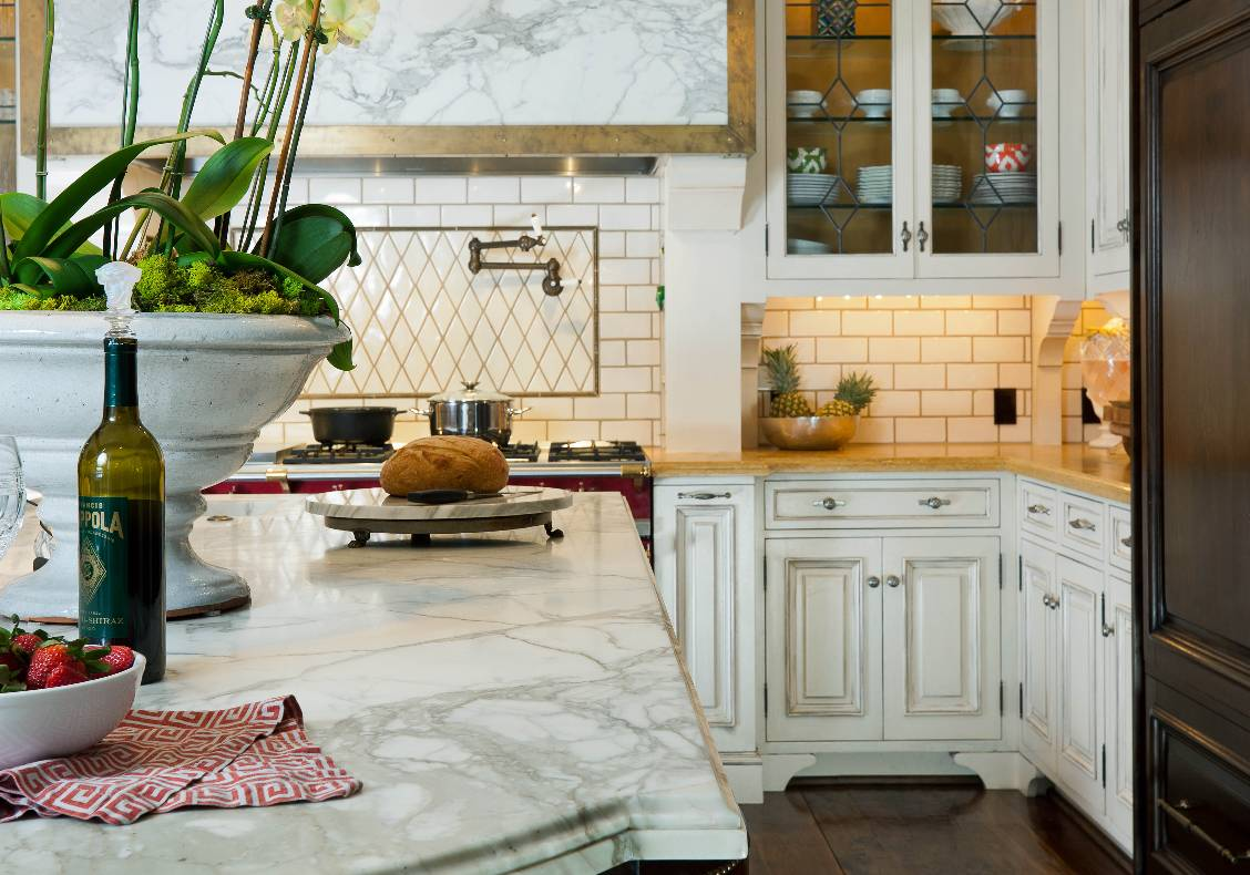 The Carrara Calacata marble top island is a counterpoint to the warm Jerusalem gold counters beneath creamy painted cabinets supported by ovulo wooden brackets.