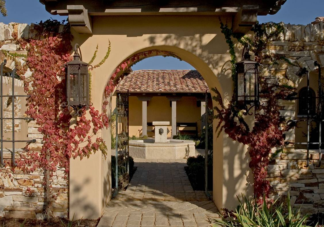 A Tuscan clay-tile roofed gate set in a rough-laid wall of of Carmel stone opens to an entry court with a central fountain surrounded by fragrant citrus trees and herbs.