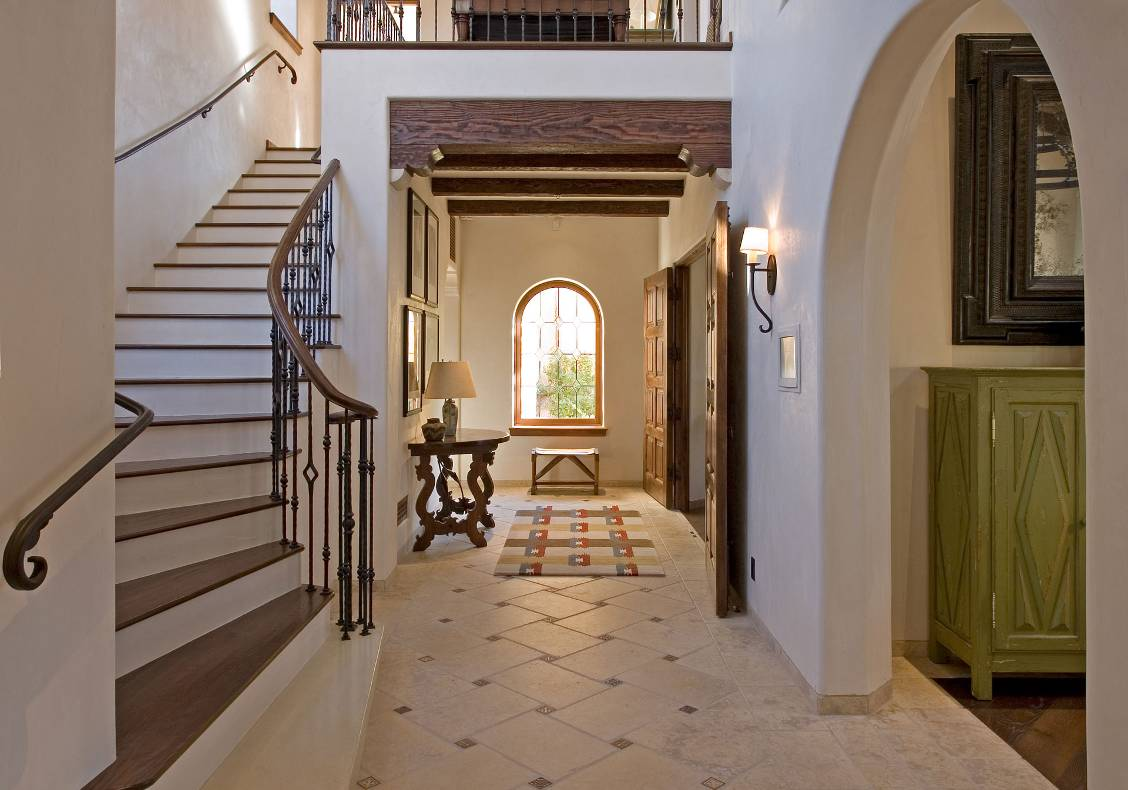 A winding stair climbs under a circular tower to the upper private bedrooms of the home.