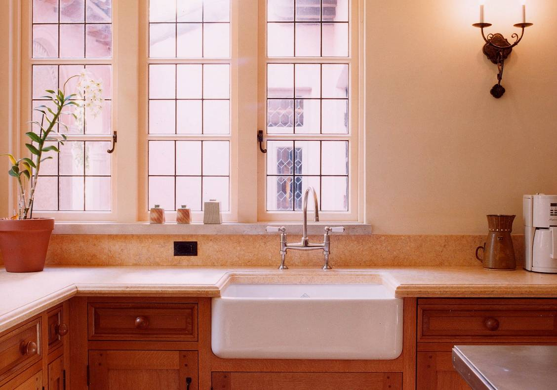 Behind the sink, a row of windows provides a view of the kitchen courtyard.