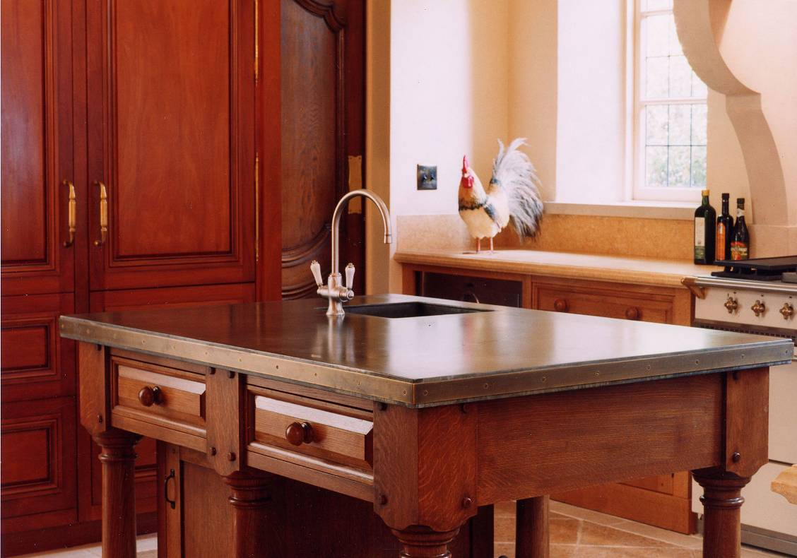 The kitchen island is designed to appear as a piece of free-standing furniture.