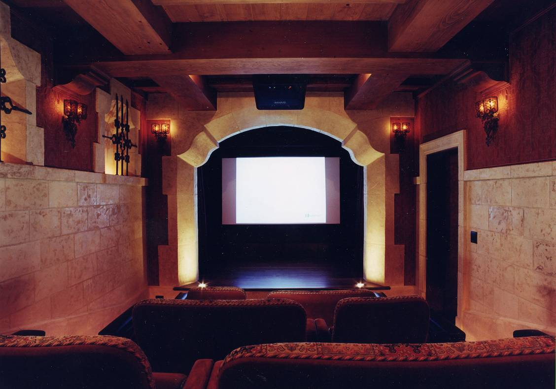 A new media room tucked under the garage resembles a traditional theatre with stage, proscenium, upholstered seats, and hand painted beamed ceiling inspired by the Basilica of Assisi.