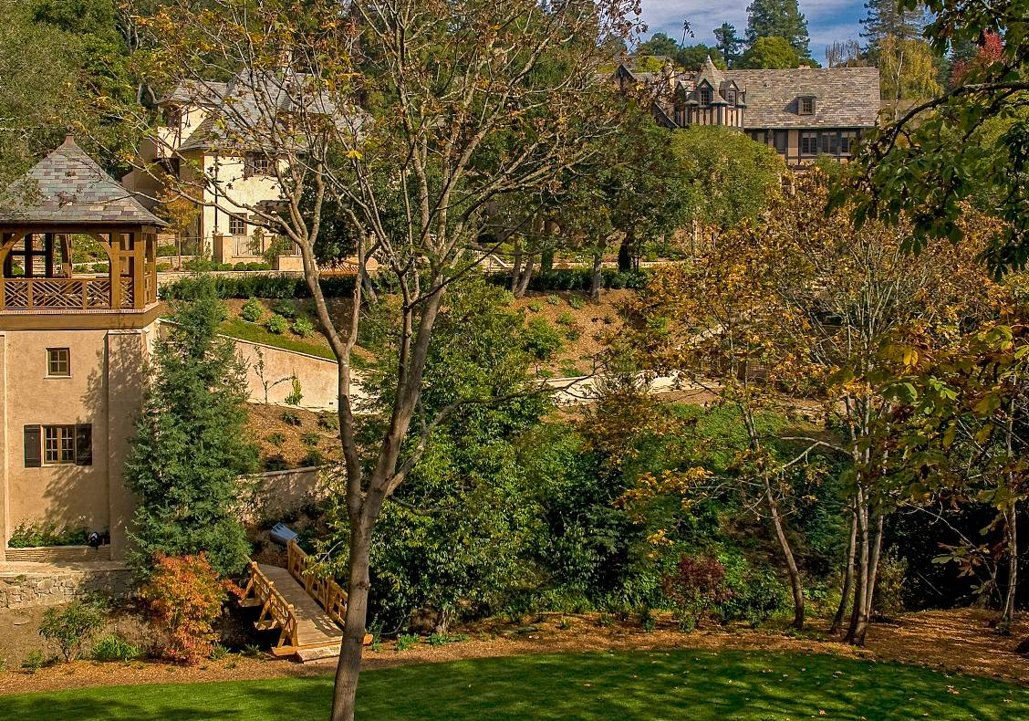 Perched like a tree house, the gazebo has beautiful, sylvan views of a brook, bridge, pool, and sport court.
