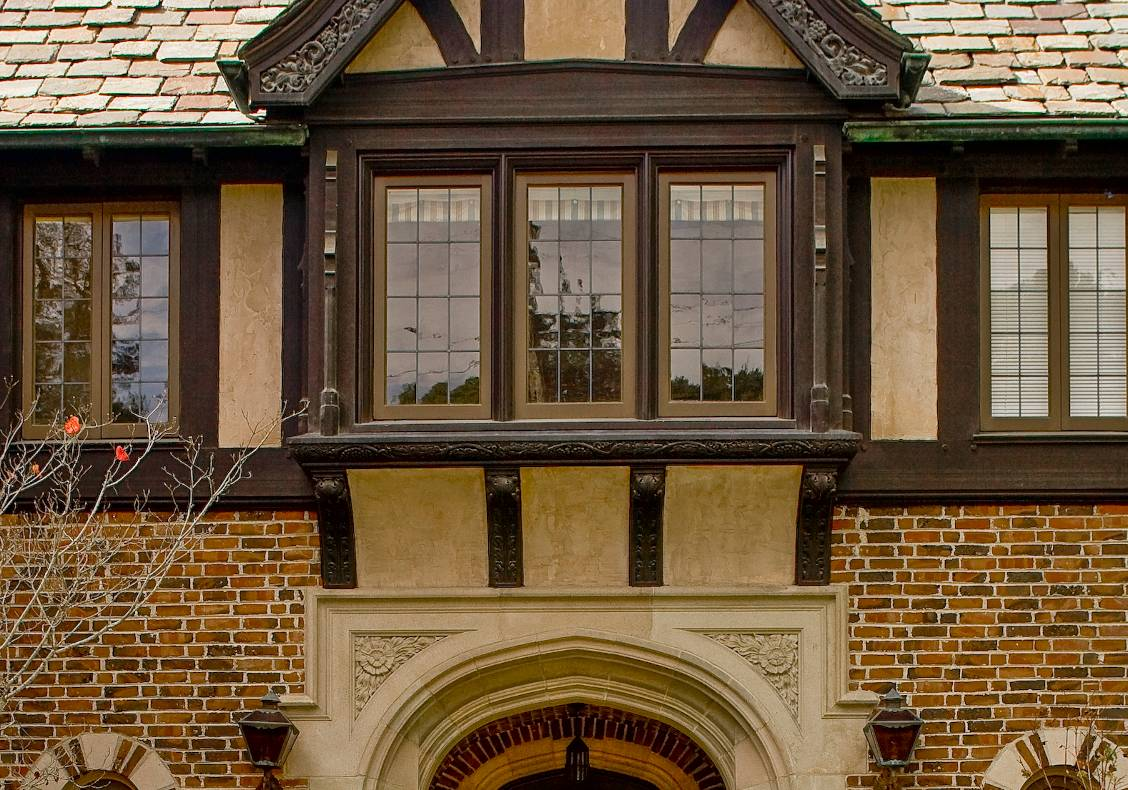 The magnificent carved stone entry portal draws the visitor inside, and blends harmoniously with the surrounding brick and timber-framed bay windows above.