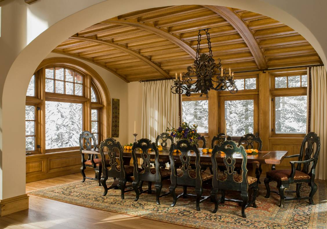 Under a pine barrel vault, the dining room opens into the main space and enjoys a cheerful view of the fireplace.
