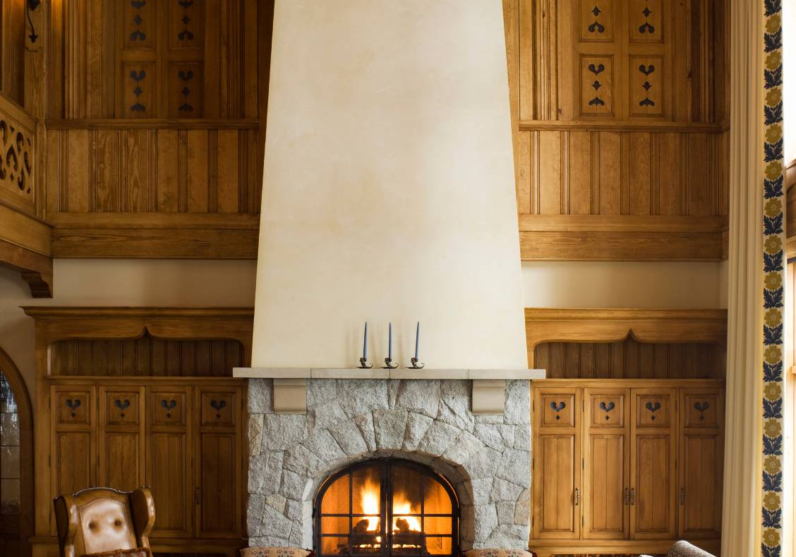 The fitted stone mantel supports a chimney that climbs two storeys to the pine ceiling.