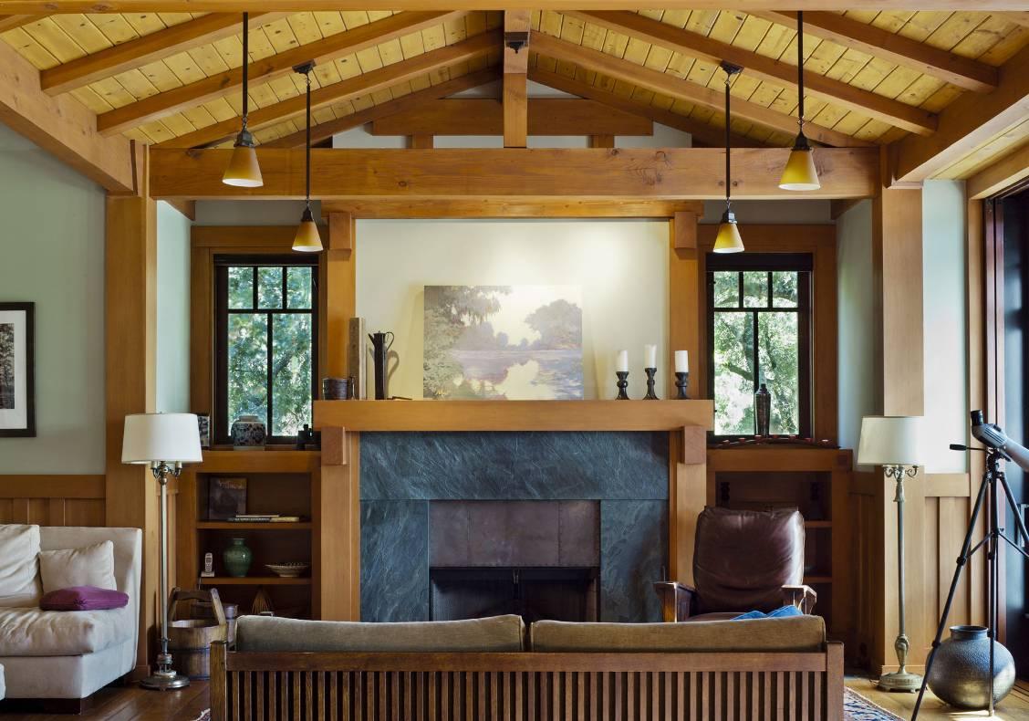 The fireplace is surrounded by black Soapstone slab, encased by a stained wood mantel with brackets, and build-in bookcases.