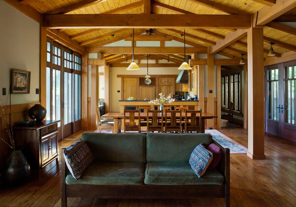 The great room unites the kitchen, dining, and living spaces under an articulated framework of intersecting beams.