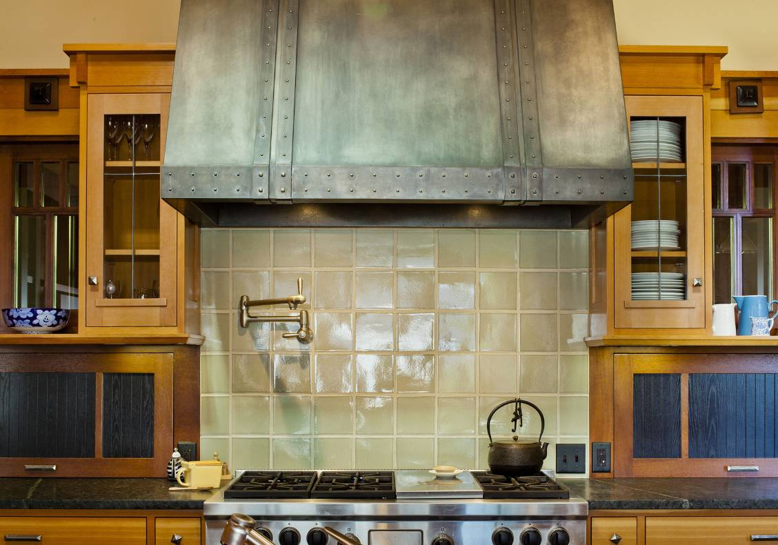 A professional stainless steel range is flanked by custom-made stained wood cabinets and black soapstone slab countertop. Hand-made ceramic tiles lined the back splash and a custom-made metal hood tops the range.