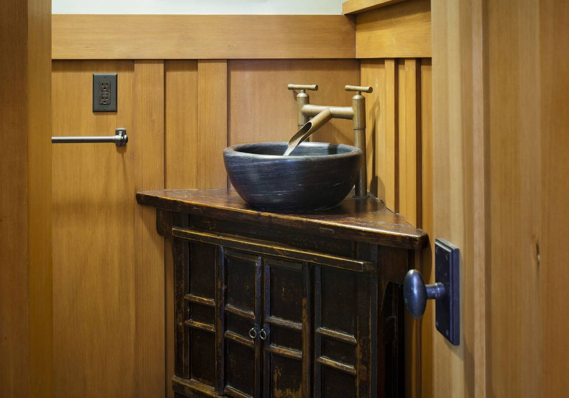 A customized antique Japanese cabinet holds a stone vessel and copper faucets. A stained wood wainscot dresses the walls.