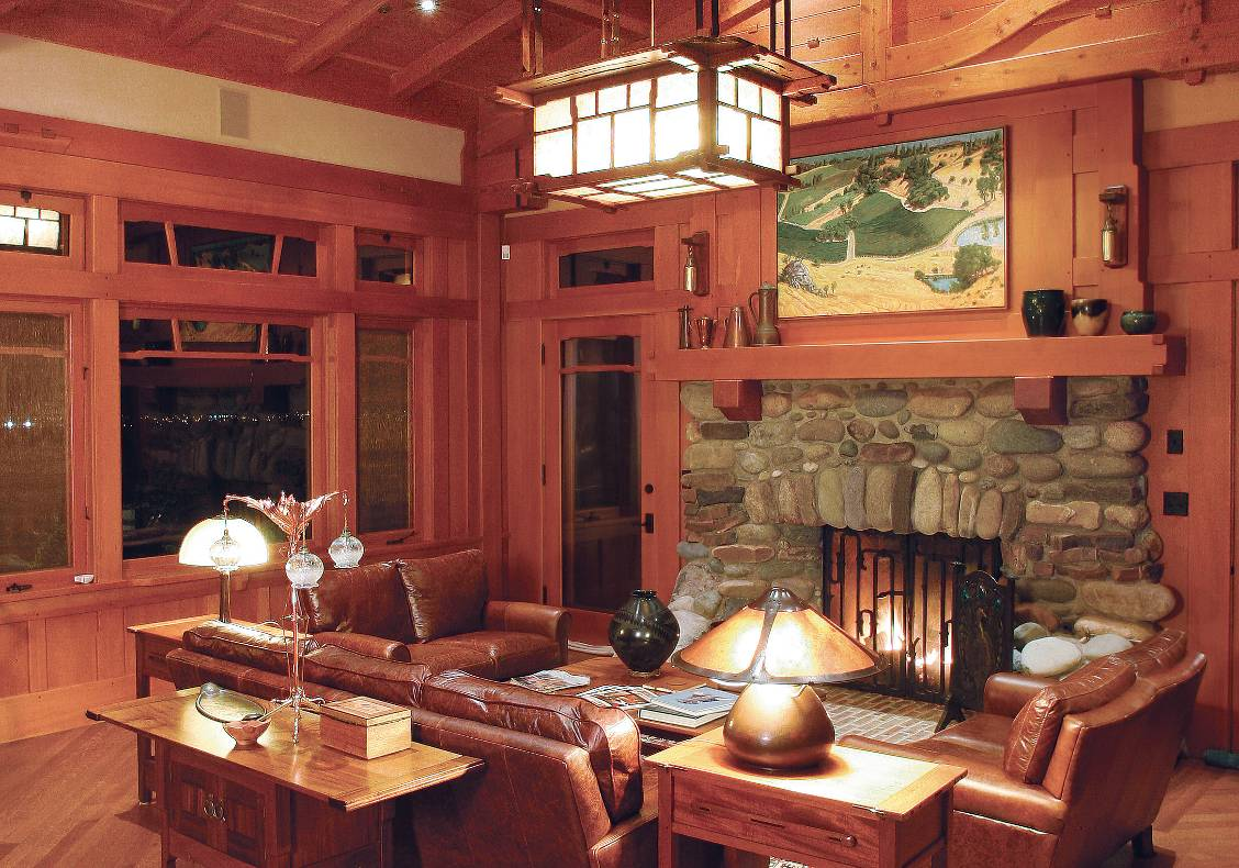 View of great room with custom designed heavy timber trusses and large 'cloud-lift' windows, rock fireplace and hand crafted iron fireplace doors.
