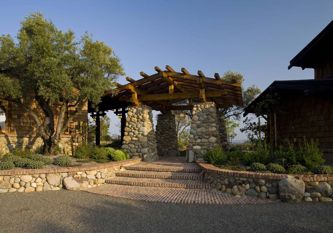 A massive stone entry pergola with reclaimed brick and stone walkway announce the entrance to the home.