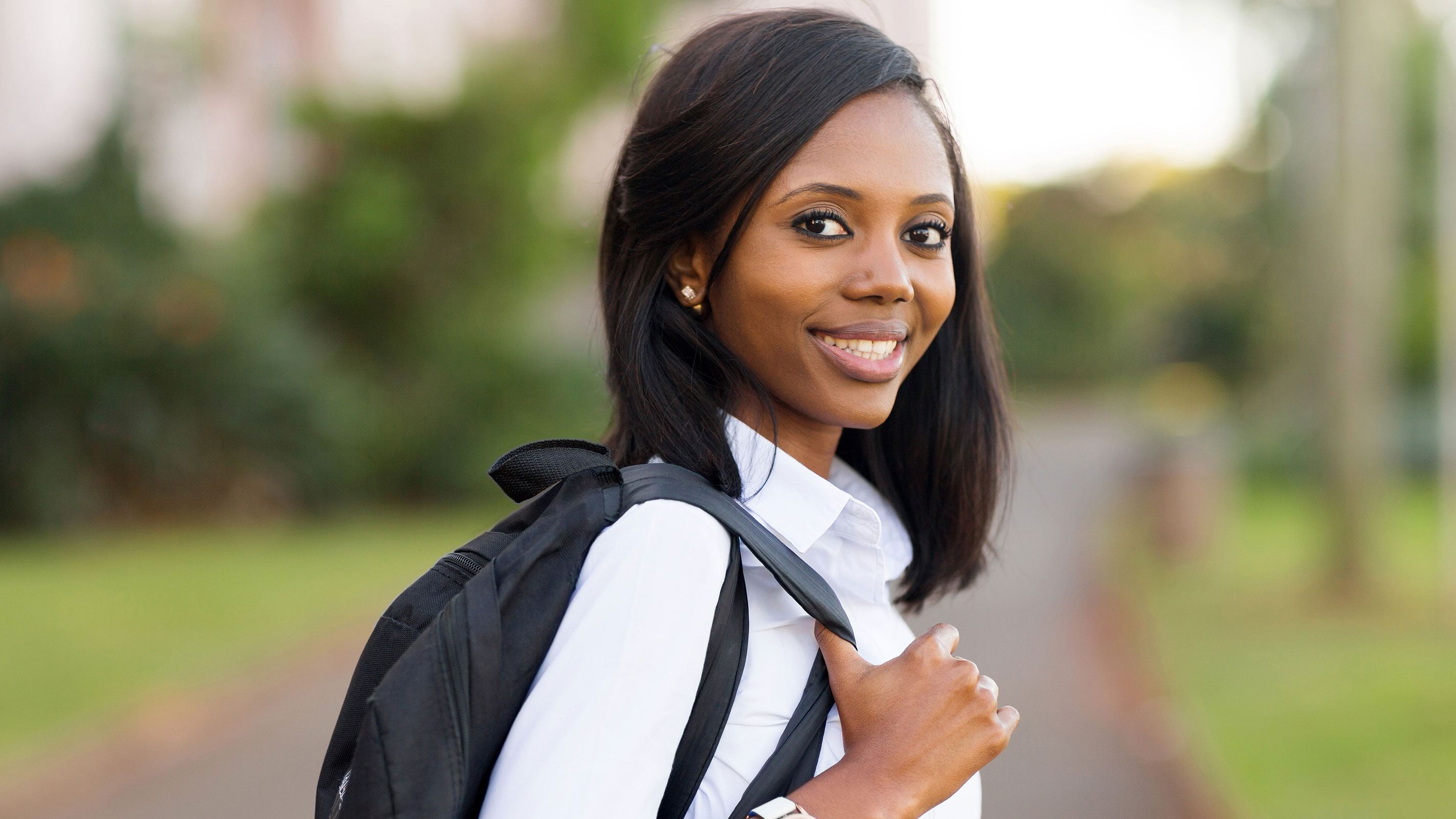 Female student holding backpack smiles at camera