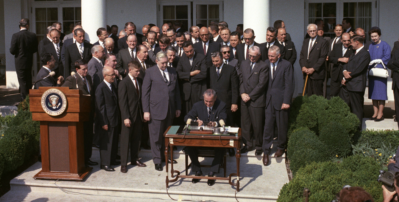 President Lyndon B. Johnson signs the Economic Opportunity Act