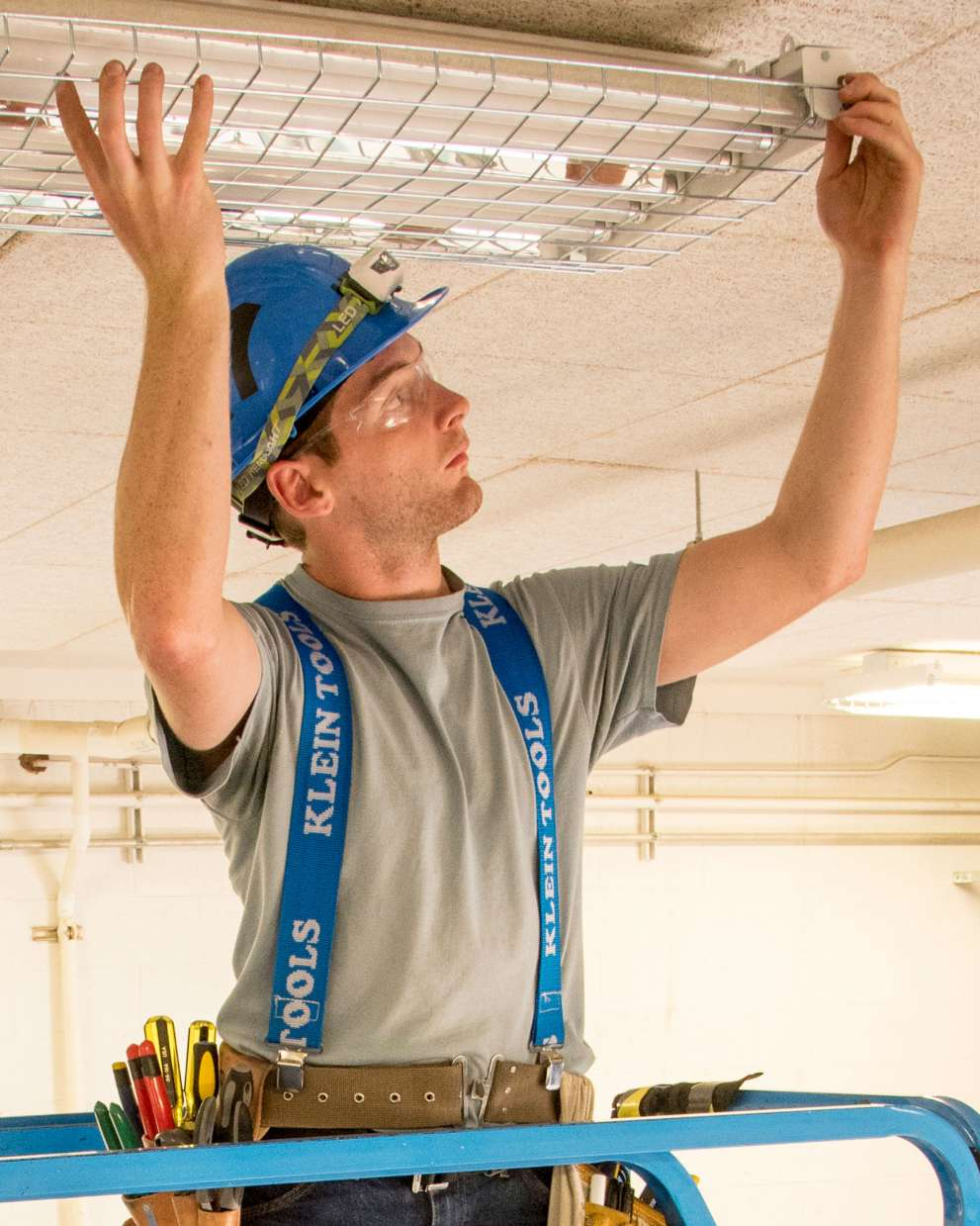 A Sign, Billboard, and Display worker installs a sign in a hallway