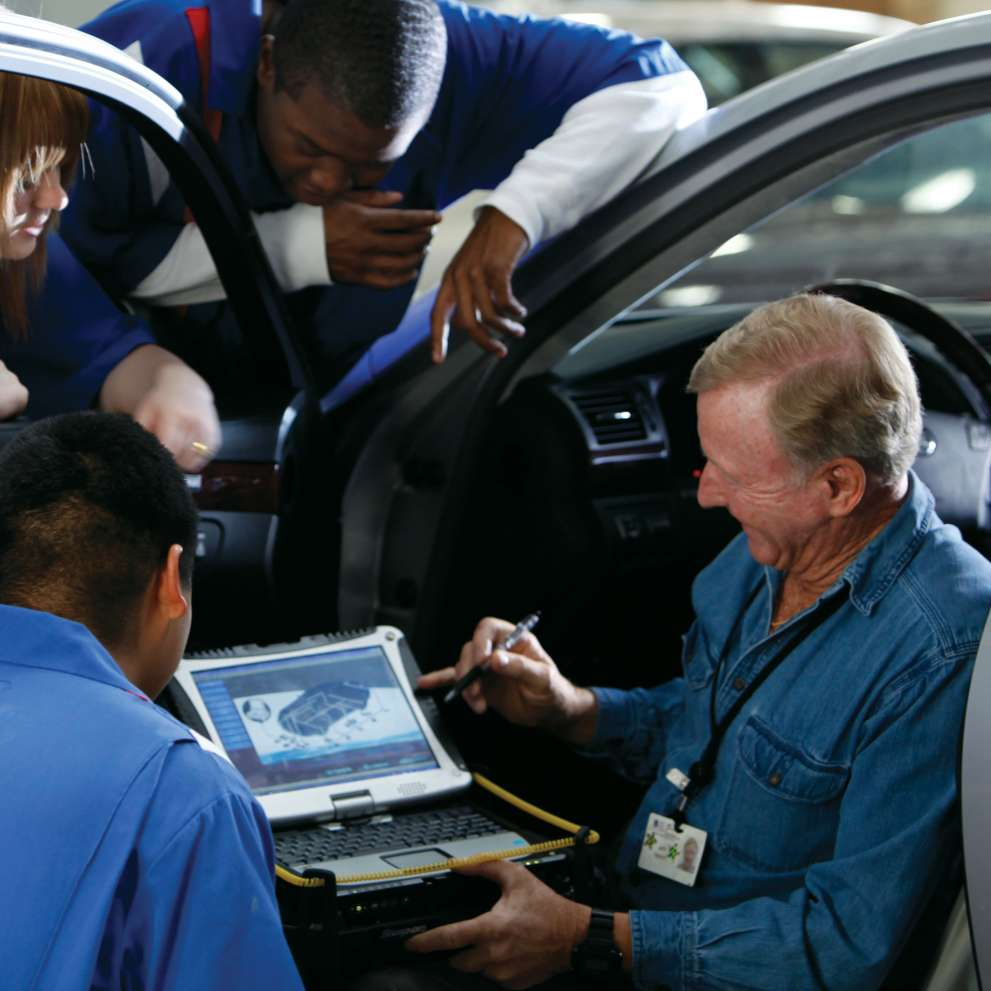 An instructor shows auto repair students a car's diagnostic screen on a laptop