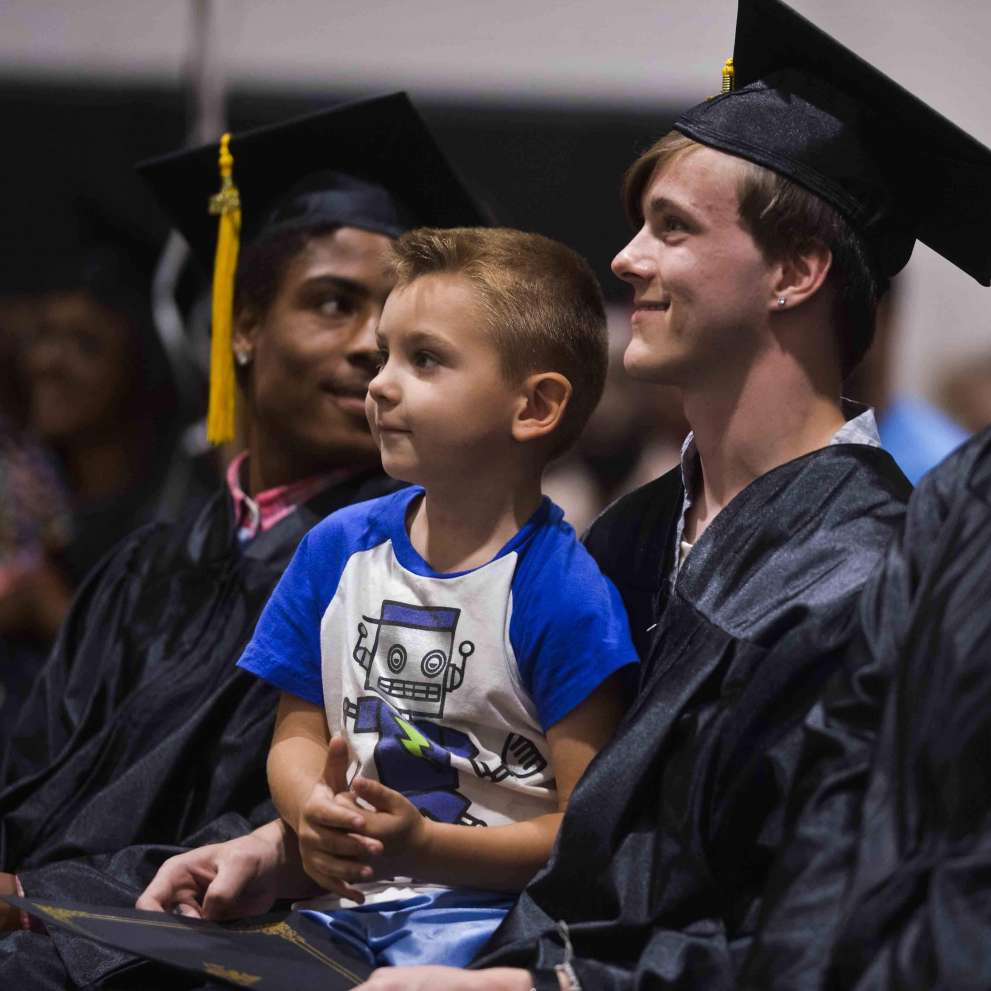 A proud graduating student holds his son in his lap.