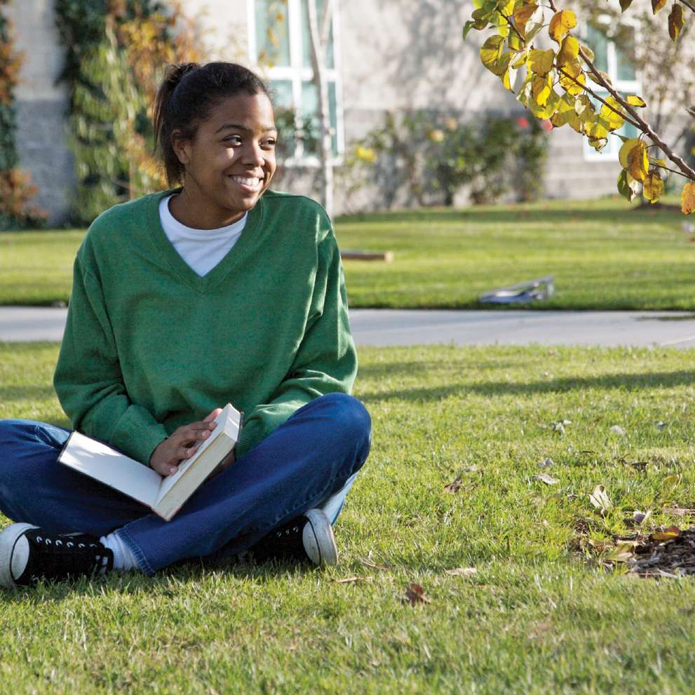 A smiling student studies outdoors on a lawn.
