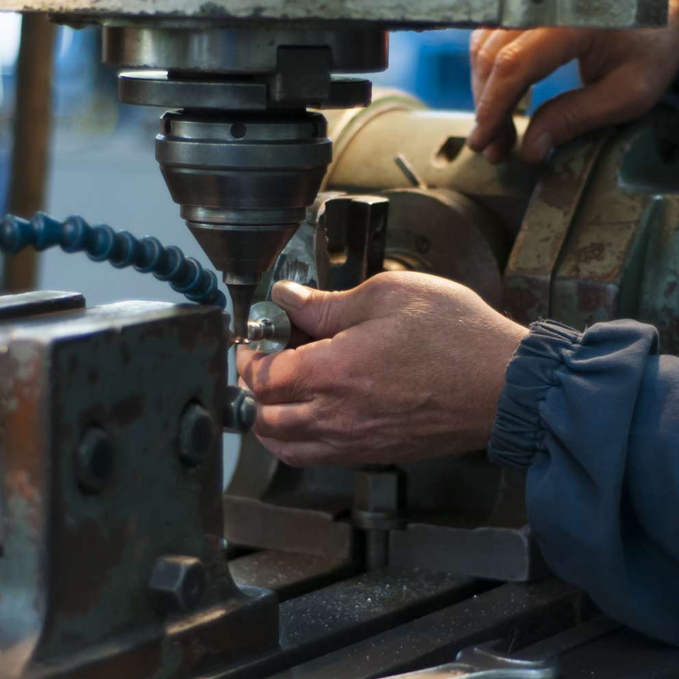 A machinist at work behind a specialized tool.