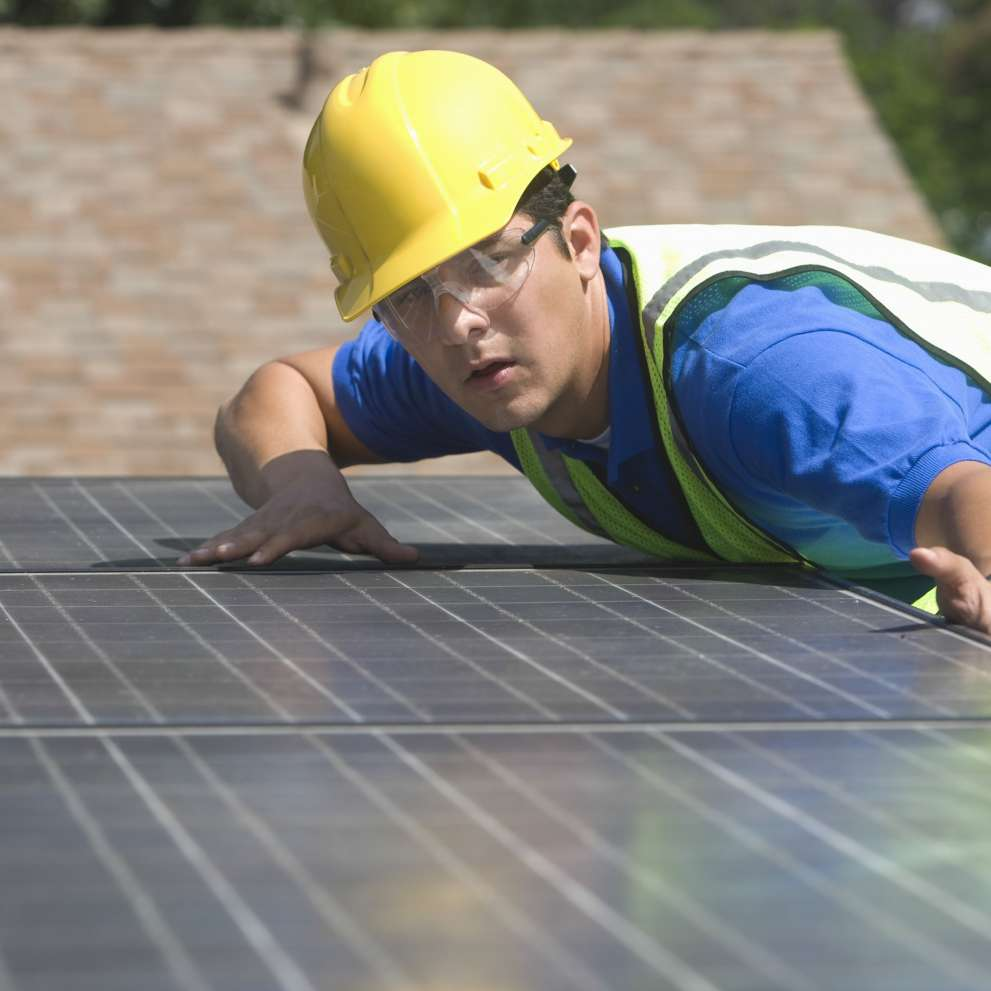 An Advanced Solar PV and Thermal System Installer inspects a solar panel installation