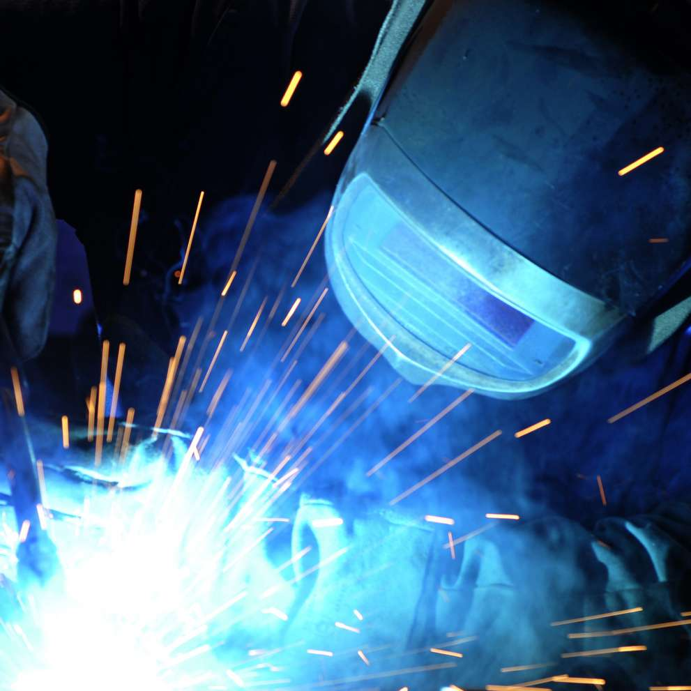 Sparks fly as a welder applies his torch to a piece of metal.