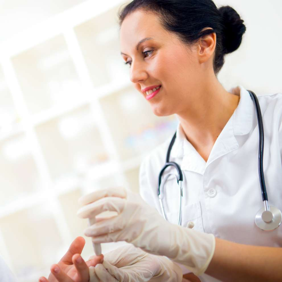 A Clinical Medical Assistant draws blood from a patient's finger.