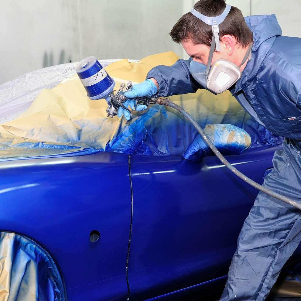 A Collision Repair and Refinish student paints a car blue.