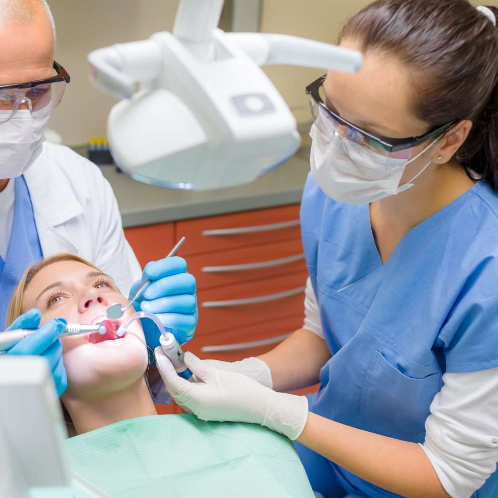 A Dental Assistant helps a dentist with a patient.