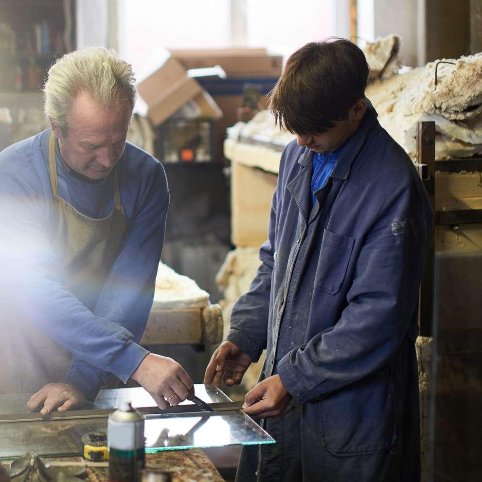 A glazier measures a piece of glass.