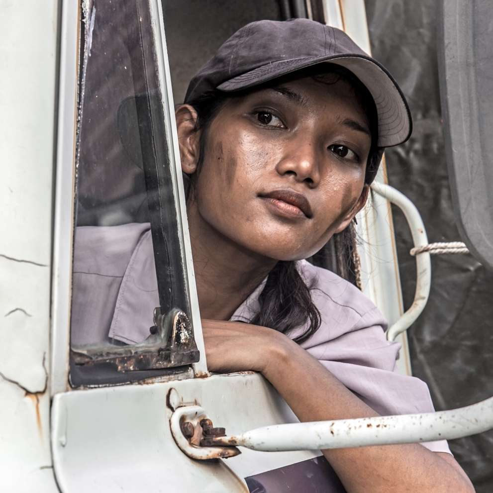 A Heavy Truck Driving woman looks at the road ahead of her